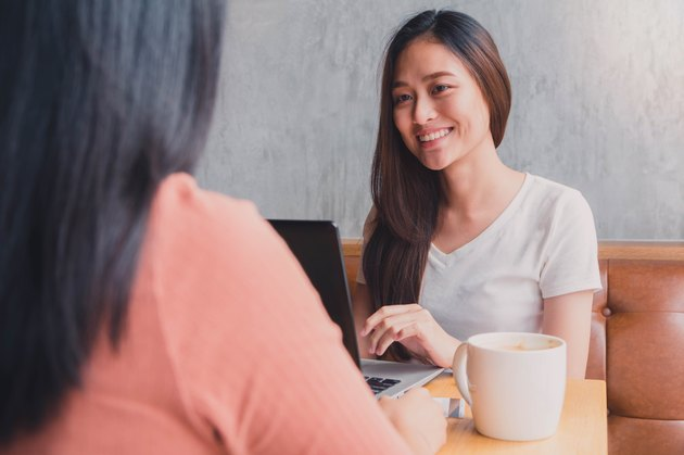 Young East Asian woman on laptop smiling at another woman over coffee