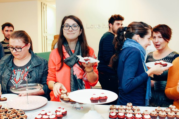 Young woman making a funny face above office party table of cupcakes