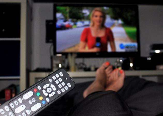 Woman with brightly painted toenails watching newscast holding remote control