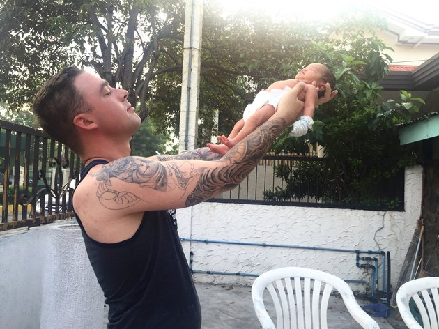 Tattooed young father holding newborn aloft on outdoor patio