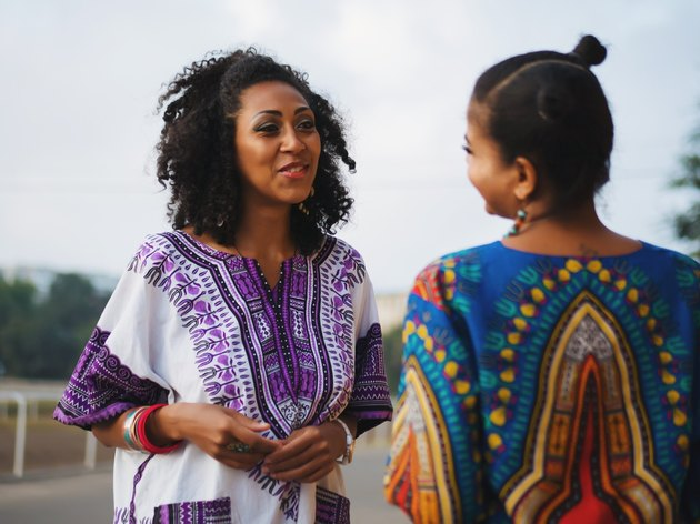 Two Black women wearing colorful shirts conversing