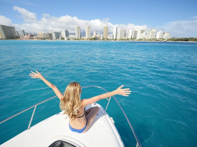 Blonde woman in bikini at front of yacht in front of Honolulu skyline