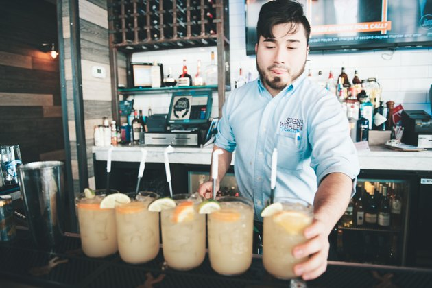Bartender serving five cocktails at bar