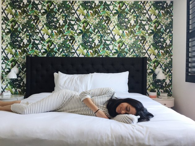Woman lying on hotel bed in front of tropical wallpaper