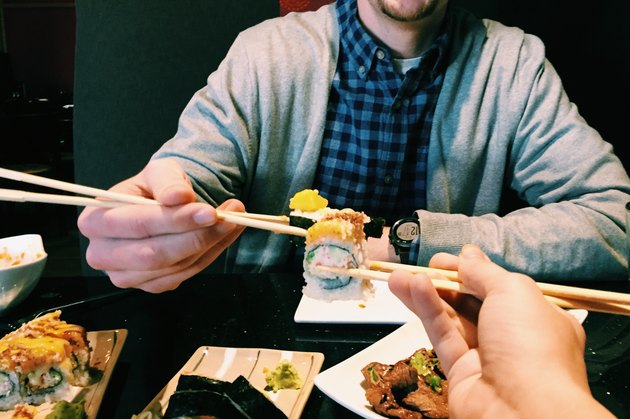 POV shot of two people eating sushi at restaurant