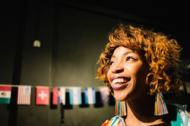 Smiling black woman in front of flags bunting