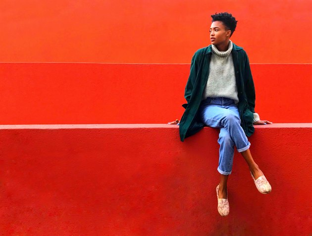 Casually dressed Black woman sitting on red wall against red background