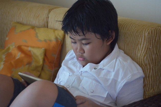 Young boy hunched over iPad