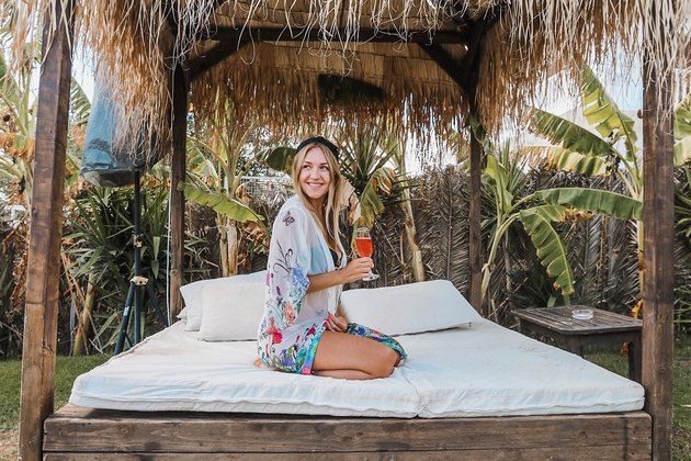 Woman sitting on canopy bed outside with fruity drink
