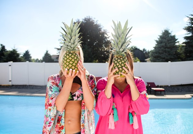 Two women by a pool holding pineapples in front of their faces