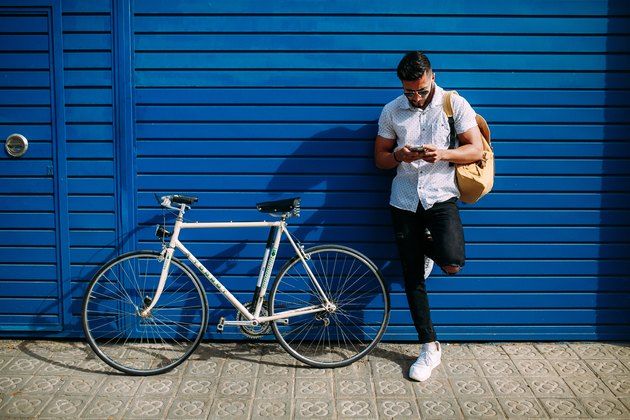 Man with bicycle against blue wall