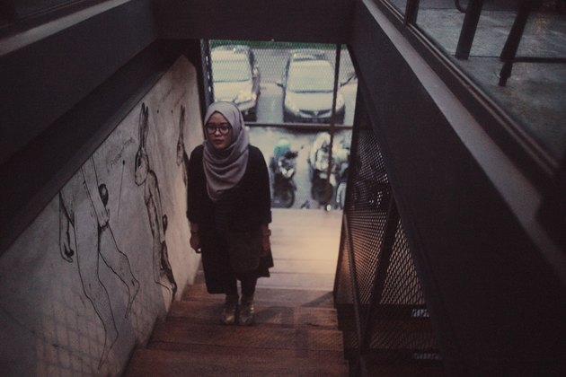 Young hijabi walking up a dim stairwell