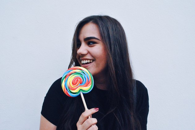 Young woman dressed in black holding rainbow lollipop