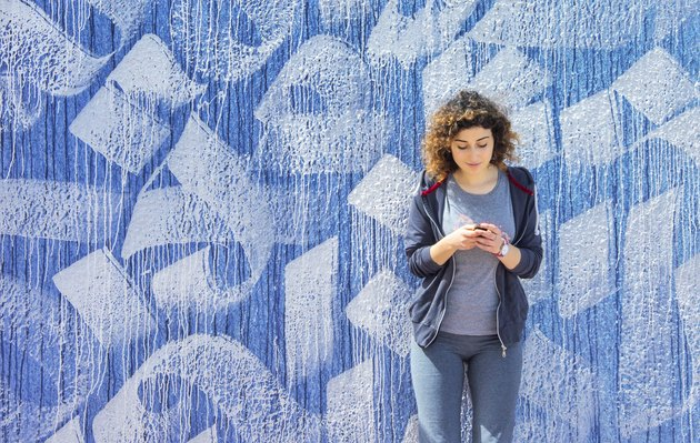 Young woman checking phone in front of blue and white mural