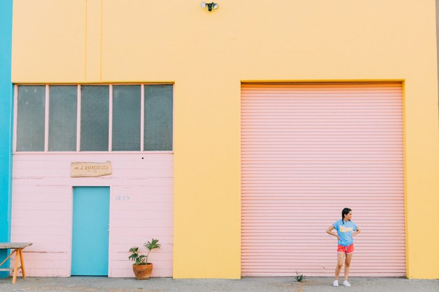 Woman stands in front of colorfully painted warehouse