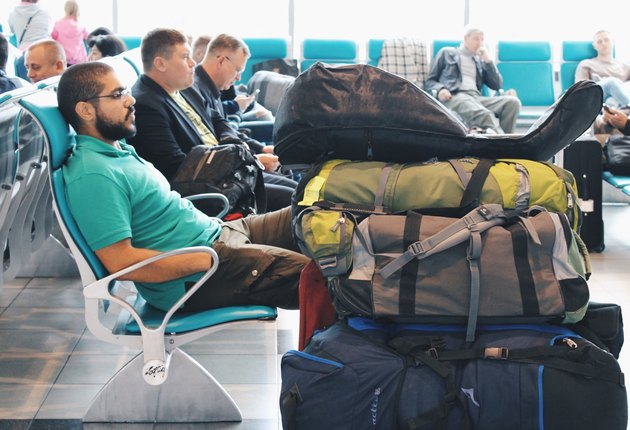 Young bearded man waiting in airport gate near piles of luggage