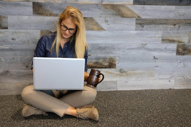 Young blonde woman sitting on floor with laptop and mug