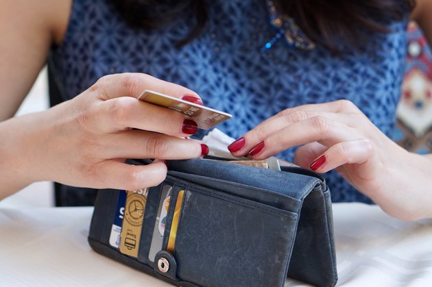 Woman with red fingernails rifling through a wallet