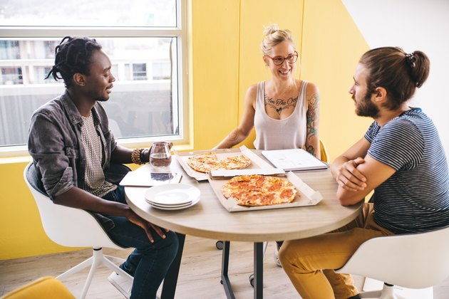 Three young professionals eating pizza around a table