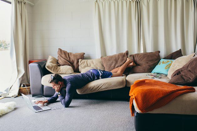 Man lying precariously on couch while reading laptop