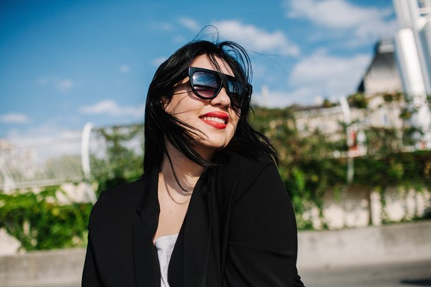 Fashionable young woman smiling outside in business casual and shades