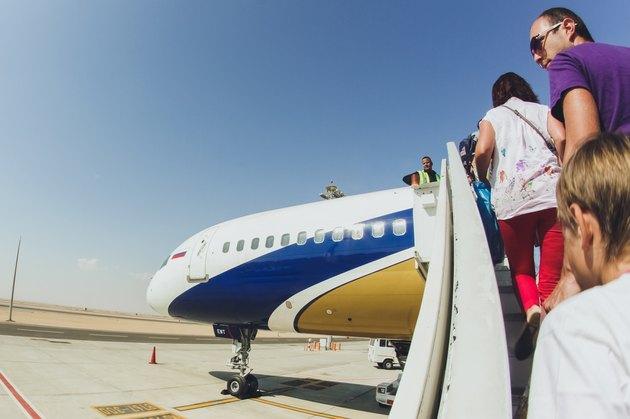 Passengers boarding airplane on tarmac