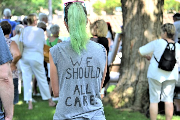 "Woman at protest wearing shirt reading ""We Should All Care"""