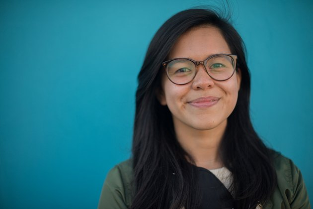 Portrait of young smiling woman in glasses against turquoise background