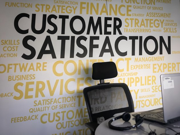 Empty office chair in front of wall emblazoned with CUSTOMER SATISFACTION
