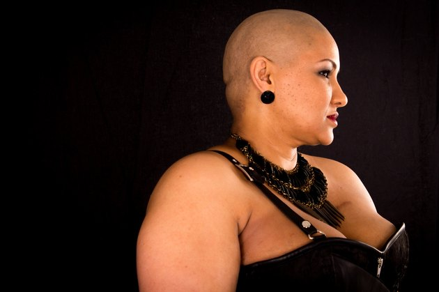 Cancer survivor with shaved head against black background