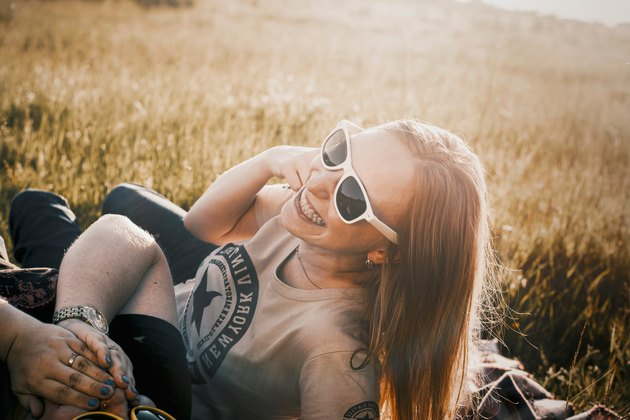 Redheaded woman in sunglasses grinning in sunlit field with friend