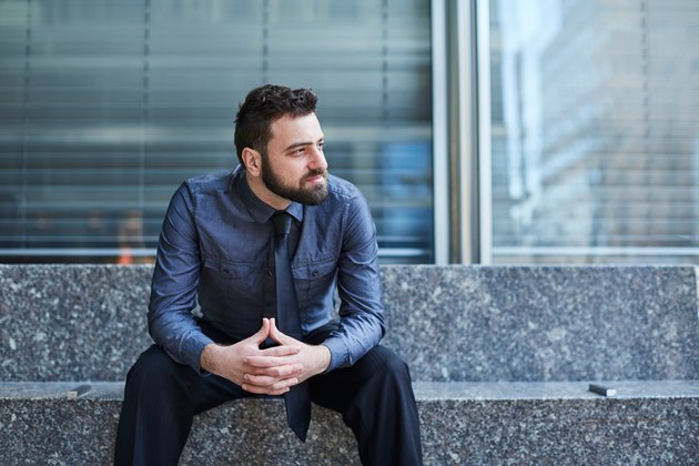 Young bearded Brazilian man leans forward confidently on a bench in the Financial District in New York City