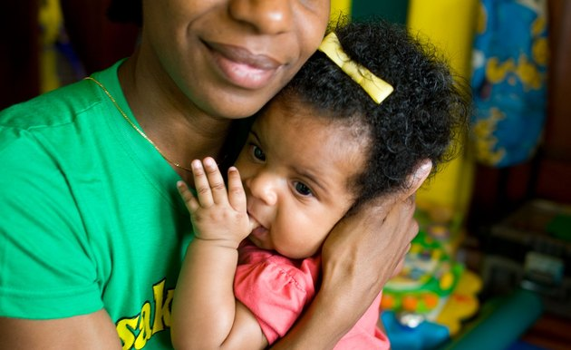 Black mother smiling as she cradles a baby girl