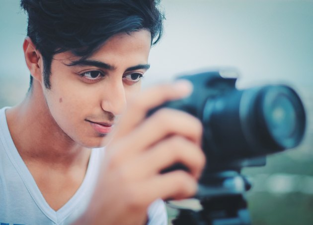 Young man behind DSLR camera on tripod