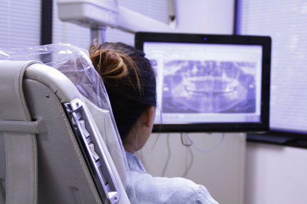 Rear view of woman in dentist's chair looking at mouth x-rays