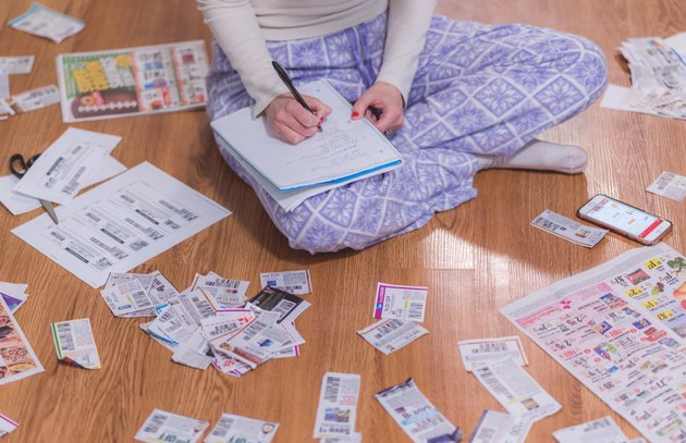 Young woman in PJs surrounded by coupon clippings