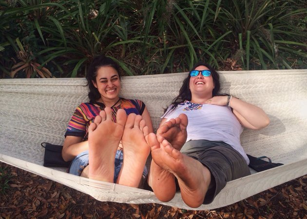 Two laughing women sharing a hammock
