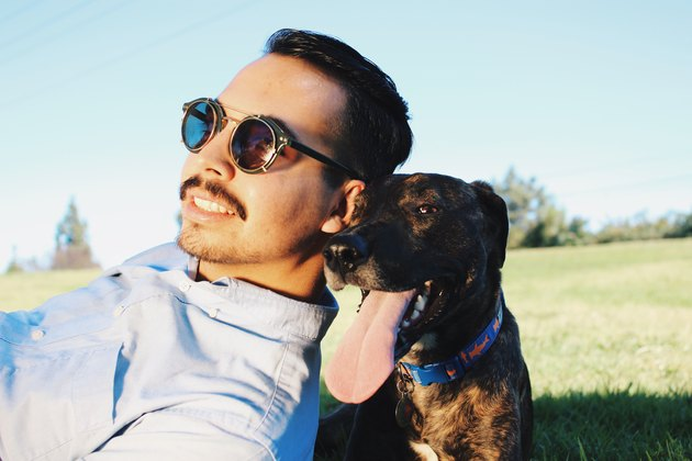 Man at park with dog posing in field