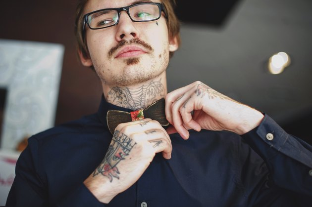 Tattooed man adjusting bow tie
