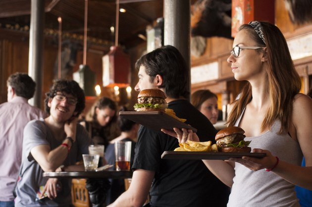 Waitress carrying plates of burgers
