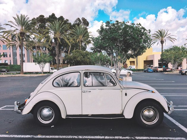 Vintage white VW Beetle in parking lot with palm trees