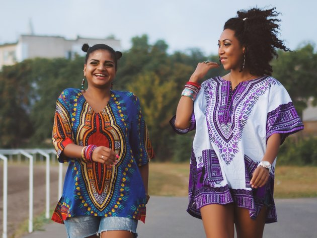 Two Black women walking together and smiling