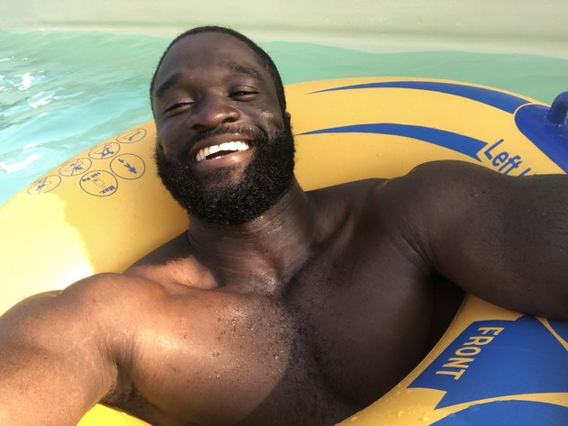 Beaming bearded Black man in swimming pool inner tube