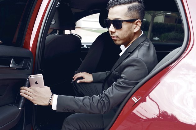 Dapper Asian man getting out of luxury car