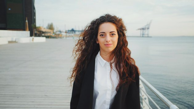 Woman with curly hair smiles on pier