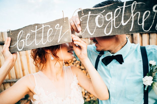 "Newlyweds holding up sign that reads ""Better Together"""