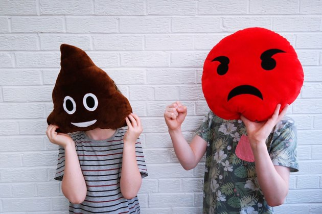 People holding up large plush poop and angry face emojis