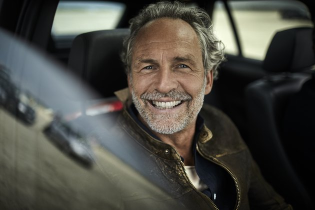 Portait of happy man with grey hair in a car