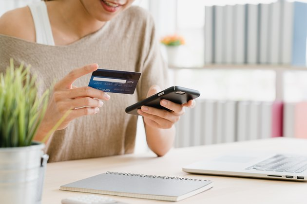 Midsection Of Woman Holding Debit Card While Using Mobile Phone For Online Shopping On Table