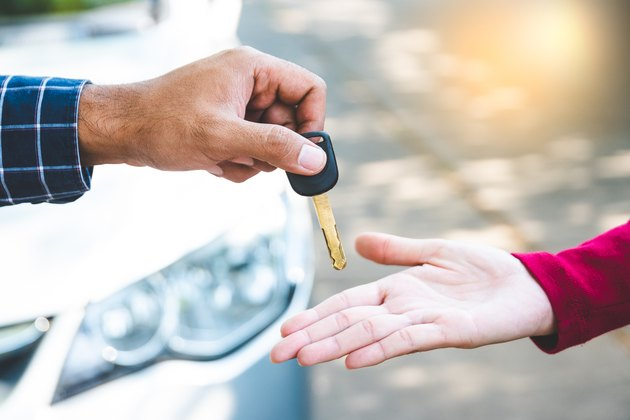Close up hand male giving a key new car on hand female outside her car. Concept of rent car or buying car.